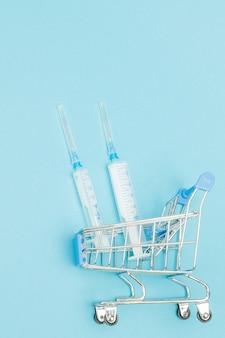 Wstrzyknięcia medyczne w wózek na zakupy na niebieskim tle