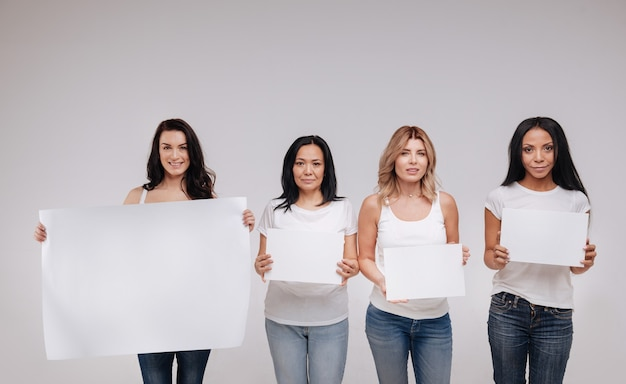 Wszyscy jesteśmy ludźmi. cudowne, atrakcyjne, nieustraszone panie stojące blisko siebie i pozujące trzymające puste plakaty