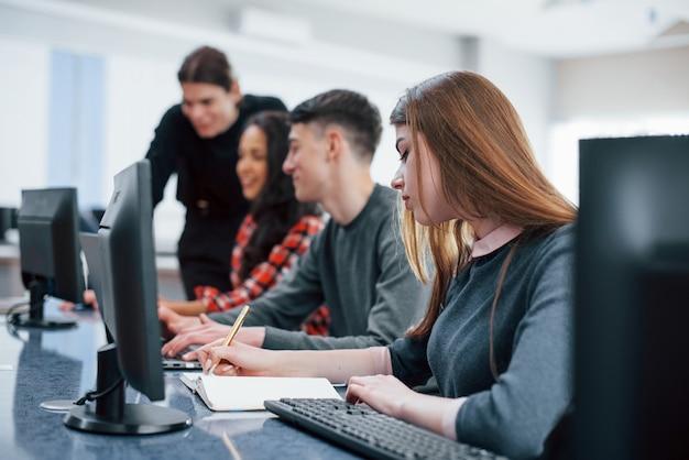 Wszyscy wykonują swoją pracę. grupa młodych ludzi w ubranie w nowoczesnym biurze