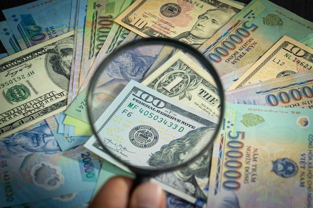 Wszystkie pieniądze w stosach dolar amerykański usd, vnd, dong pay, wymiana wietnamska i lupa patrząc na liczby