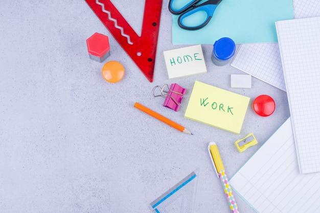 Wszystkie rodzaje narzędzi biurowych lub szkolnych na szarym tle.
