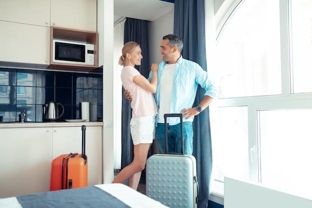 Wszystkie rzeczy zapakowane. szczęśliwy mąż i żona stoją przy dużym oknie w swoim mieszkaniu z zapakowanymi rzeczami podróżnymi przed wspólnym wyjazdem na wakacje.