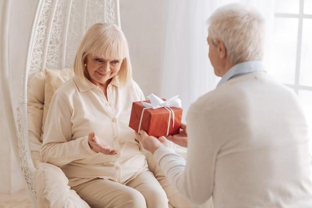 Wszystkiego najlepszego. miły, troskliwy mąż w podeszłym wieku trzyma pudełko i daje żonie prezent podczas obchodów urodzin