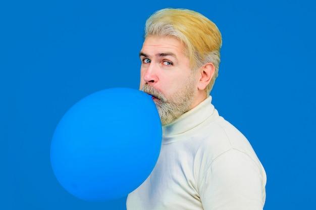 Wszystkiego najlepszego stylowy brodaty mężczyzna dmuchający niebieskim balonem atrakcyjny mężczyzna przygotowuje się na imprezę