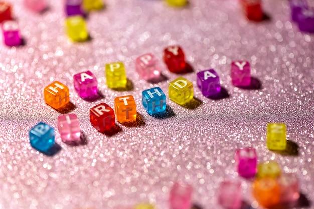 Wszystkiego najlepszego z kolorowych bloków liter na tle różowy brokat. pocztówka z okazji.