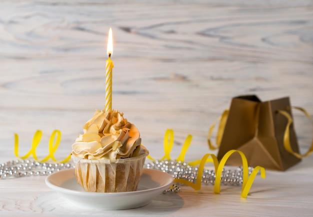 Wszystkiego najlepszego z okazji urodzin babeczka z zapaloną świeczką i prezentem