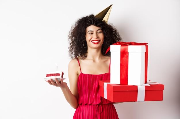 Wszystkiego najlepszego z okazji urodzin dziewczyna w czerwonej sukience, obchodzi i trzyma prezenty z bday tort, stojąc na białym tle.