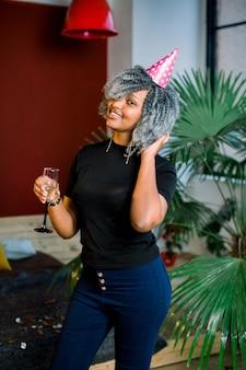 Wszystkiego najlepszego z okazji urodzin. dziewczyna z konfetti i szampanem na imprezie. portret piękna uśmiechnięta afrykańska kobieta w urodzinowym kapeluszowym trzyma szampanie w rękach, świętuje wakacje. wysoka rozdzielczość.