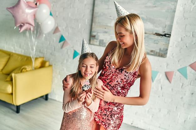 Wszystkiego najlepszego z okazji urodzin! dziewczyna zdmuchująca świeczki na urodzinowym torcie, ładna mama i urocza urocza córeczka noszą podobną odświętną sukienkę i urodzinowe czapki. rodzinne cudowne chwile.