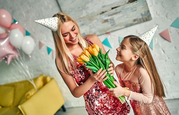 Wszystkiego najlepszego z okazji urodzin! mama gratuluje córce i daje jej kwiaty, ładna mama i urocza urocza córeczka noszą podobną odświętną sukienkę i urodzinowe czapeczki. rodzinne cudowne chwile.
