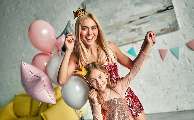 Wszystkiego najlepszego z okazji urodzin! matka i córka bawią się razem i trzymają papierowe korony, ładna mama i urocza urocza córka noszą podobne odświętne sukienki i urodzinowe czapki. rodzinne cudowne chwile.