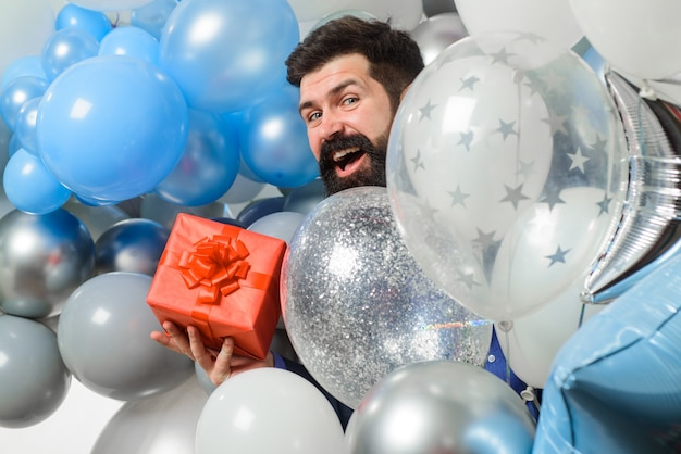 Wszystkiego najlepszego z okazji urodzin mężczyzna z balonami z helem trzyma pudełko na prezent świąteczne wydarzenie lub przyjęcie urodzinowe szczęśliwy brodaty