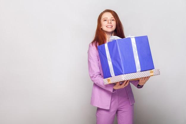Wszystkiego najlepszego z okazji urodzin! rudowłosa śliczna dziewczyna trzyma swoje prezenty i ma szczęśliwy wygląd. zdjęcia studyjne