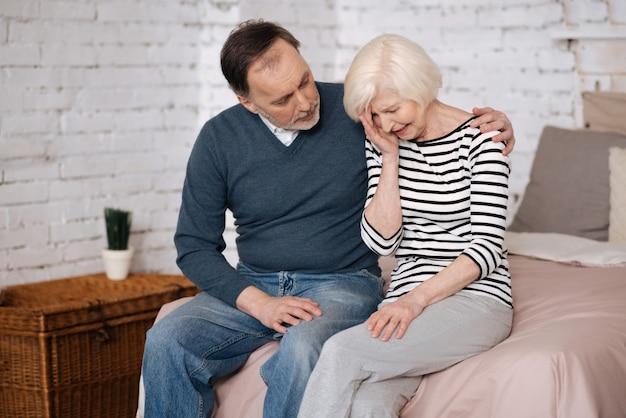 Wszystko będzie dobrze. starzec przytula i podtrzymuje płaczącą żonę, siedząc na łóżku w domu.