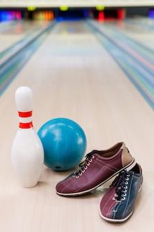 Wszystko, czego potrzebujesz do gry w kręgle. zbliżenie na buty do kręgli, niebieską piłkę i szpilkę leżące na kręgielni