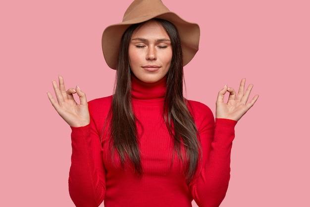 Wszystko jest perfekcyjne. zrelaksowana piegowata kobieta ubrana w kapelusz i czerwony golf