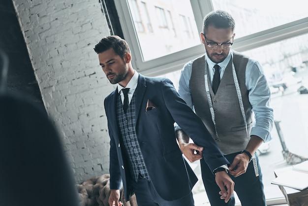 Wszystko musi być idealne. młody modny projektant pomagający swojemu klientowi się ubrać