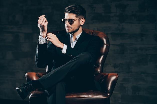 Wszystko musi być idealne. młody przystojny mężczyzna w garniturze i okularach przeciwsłonecznych dopasowuje rękaw koszuli, siedząc w skórzanym fotelu na ciemnoszarym tle