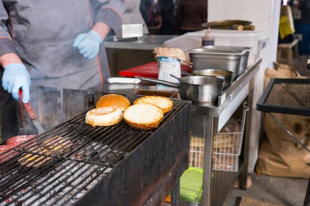Wszystko nie do poznania osoba gotująca hamburgery na grillu na gorący węgiel drzewny z naciskiem na bułki opiekania na górnym stojaku w kuchni restauracji