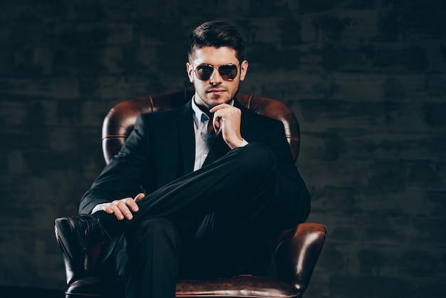 Wszystko o stylu. młody przystojny mężczyzna w garniturze i okularach przeciwsłonecznych, trzymając rękę na brodzie i patrząc na kamerę, siedząc w skórzanym fotelu na ciemnoszarym tle
