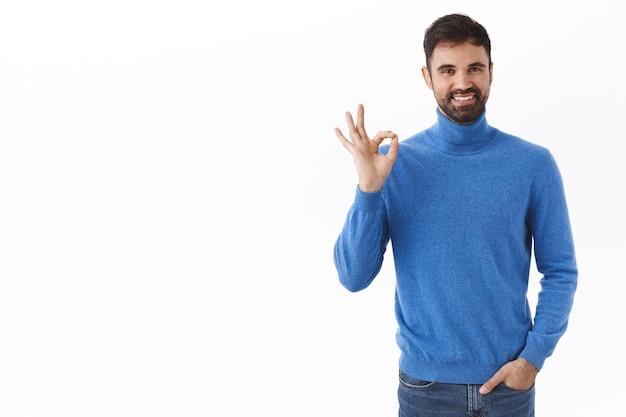 Wszystko pod kontrolą. portret udanego szczęśliwego kaukaskiego, męskiego przedsiębiorcy z brodą, dobrze się pokaż, dobrze gest i uśmiechnij się zadowolony, polecam dobrej jakości produkt, biała ściana