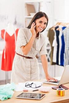 Wszystko pod kontrolą. szczęśliwa młoda kobieta rozmawia przez telefon komórkowy i pracuje na laptopie, stojąc w warsztacie mody
