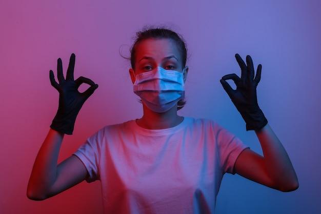 Wszystko pod kontrolą. zrelaksowana kobieta w masce medycznej i rękawiczkach pokazuje symbol porządku. czerwono-niebieskie neonowe światło gradientowe