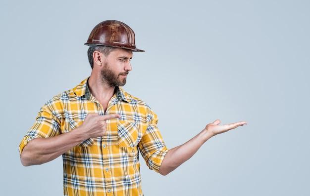 Wszystko powinno być idealne. architekt mężczyzna prezentując produkt. facet nosić mundur pracownika. budowniczy w kasku. dojrzały mężczyzna nosić koszulę w kratkę. profesjonalny konstruktor lub mechanik. inżynier budowniczy.