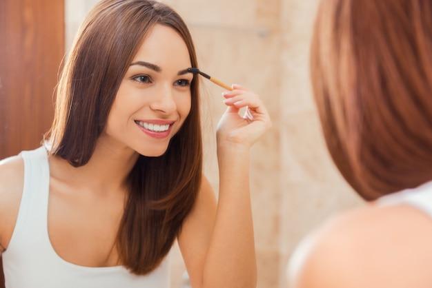 Wszystko powinno być idealne. atrakcyjna młoda kobieta robi makijaż, patrząc w lustro i uśmiechając się