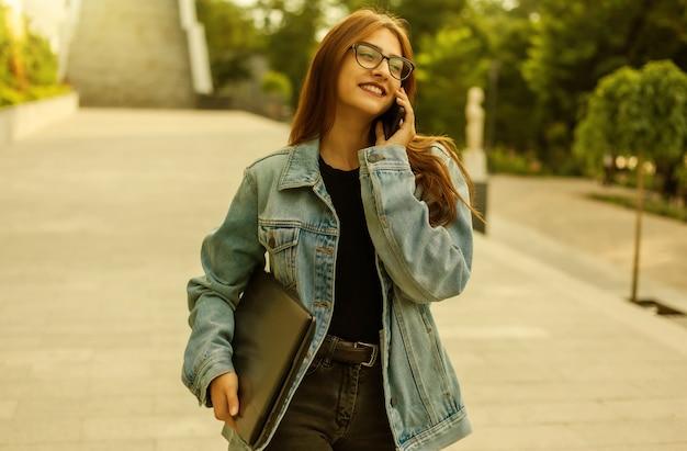 Wszystko w biznesie. młoda stylowa kobieta w dżinsowej kurtce i okularach, trzymając laptopa i rozmawiając przez telefon podczas spaceru po mieście.
