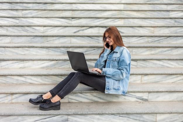 Wszystko w biznesie. młoda stylowa kobieta w dżinsowej kurtce i szkłach używa laptopu i rozmawia przez telefon podczas gdy siedzący na schodach w mieście. praca zdalna.