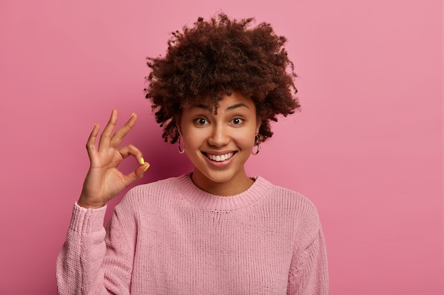 Wszystko w porządku. pozytywna, urocza afroamerykanka robi dobry gest, wyraża zgodę, zgadza się z czymś, nosi swobodny sweter, mówi `` tak '' nowym możliwościom, jest zadowolona z nowej koncepcji