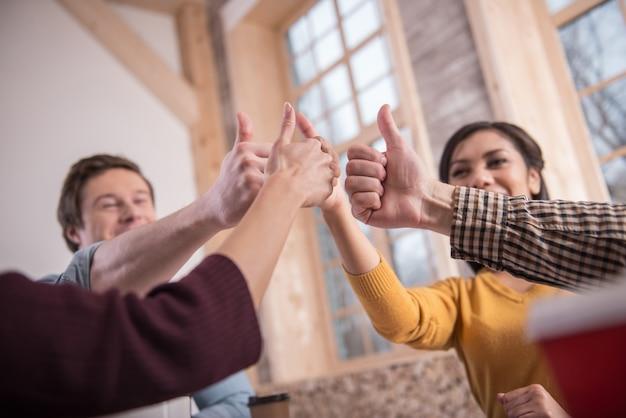 Wszystko w porządku. zbliżenie gestów kciuka w górę, jednocześnie ciesząc się z ich sukcesu
