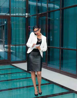 Wszystko w pracy. młody biznes afro kobieta rozmawia przez telefon i pisze ważne informacje do notatnika