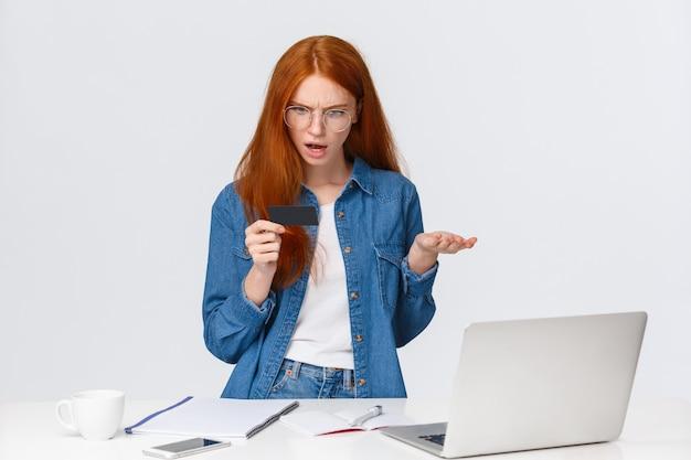 Wtf dzieje się dalej. skołatana i sfrustrowana młoda dziewczyna próbuje zapłacić za zamówienie, wygląda na zaniepokojoną i zakłóconą kartę kredytową, wzrusza ramionami z konsternacją, nie wiem, dlaczego płatność anulowana, stań w pobliżu laptopa