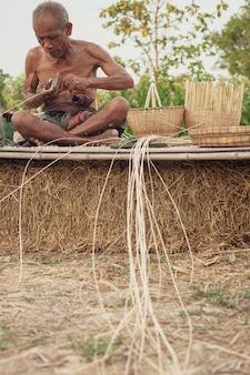 Wujek azjatycki starzec z narzędziami wikliny.