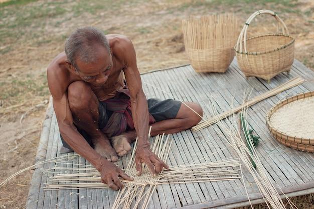 Wujek azjatycki starzec z wiklinowymi narzędziami.