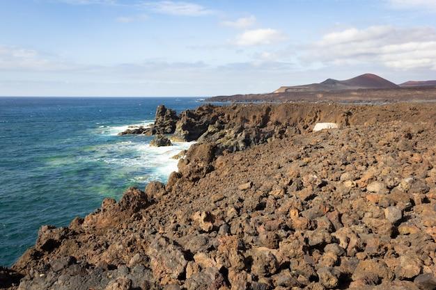 Wulkaniczne wybrzeże z błękitnymi falami oceanu atlantyckiego rozpryskującymi się na skałach na lanzarote