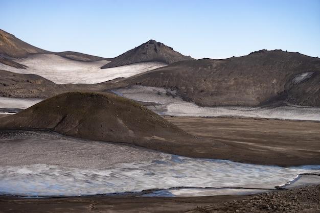 Wulkaniczny krajobraz ze śniegiem, skałami i popiołem