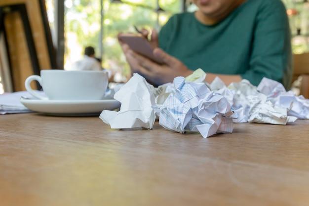 Wwoman ręka używać telefon komórkowego pracuje po godzin z zmiętym papierem na stole.