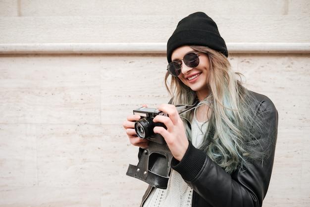 Wwoman w ciepłych ubraniach i okularach przeciwsłonecznych z kamerą retro