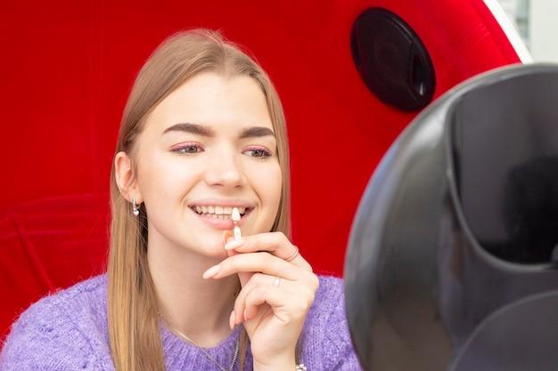 Wybielanie zębów dziewczyna podnosi odcień zębów patrząc w lustro