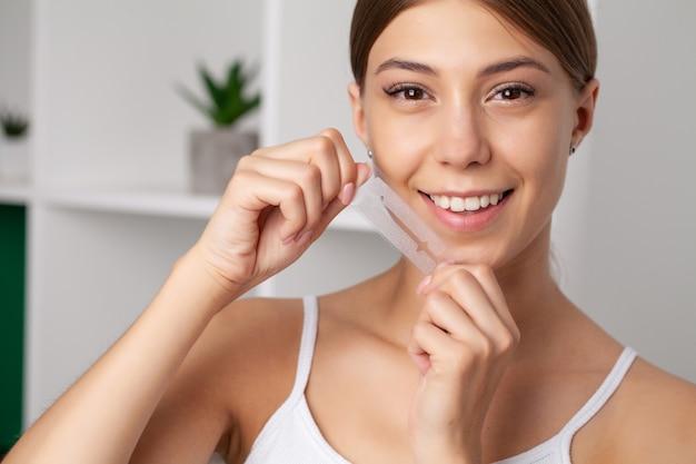 Wybielanie zębów, piękna uśmiechnięta kobieta trzyma pasek wybielający.