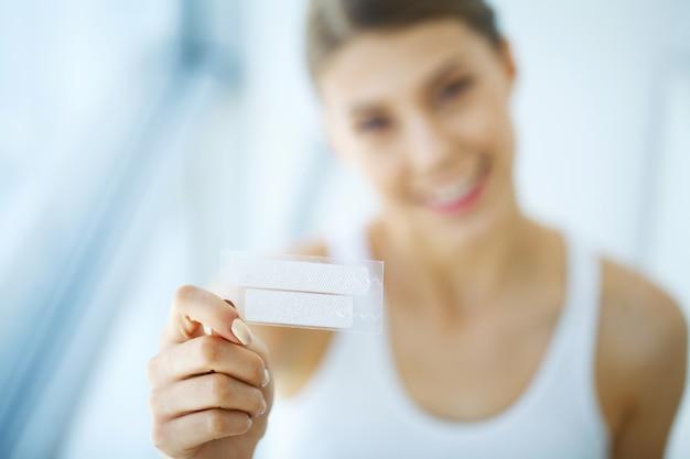 Wybielanie zębów. piękna uśmiechnięta kobieta trzyma pasek wybielający.