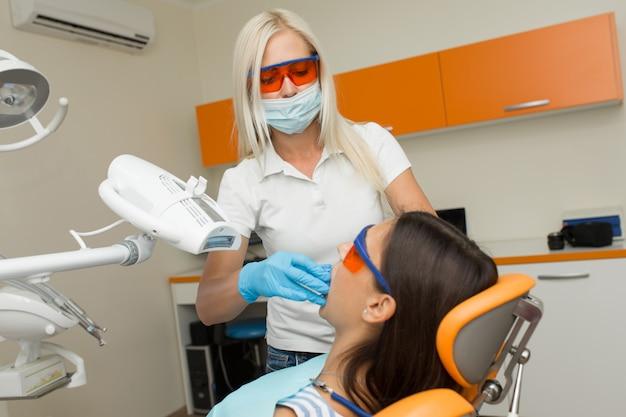 Wybielanie zębów za pomocą stomatologicznego urządzenia wybielającego uv, asystent dentystyczny opiekujący się pacjentem, oczy chronione okularami. leczenie wybielające światłem, laserem, fluorem. sztuczne wybielanie zębów