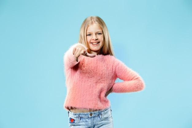 Wybieram cię i zamawiam. uśmiechnięta dziewczyna nastolatka wskazując na aparat, portret zbliżenie w połowie długości na niebiesko