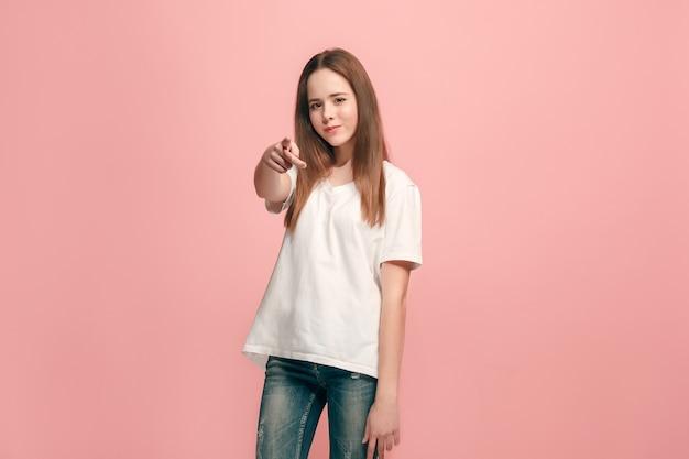 Wybieram cię i zamawiam. uśmiechnięta dziewczyna nastolatka wskazując na aparat, portret zbliżenie w połowie długości na tle różowego studia. ludzkie emocje, koncepcja wyrazu twarzy. przedni widok. modne kolory