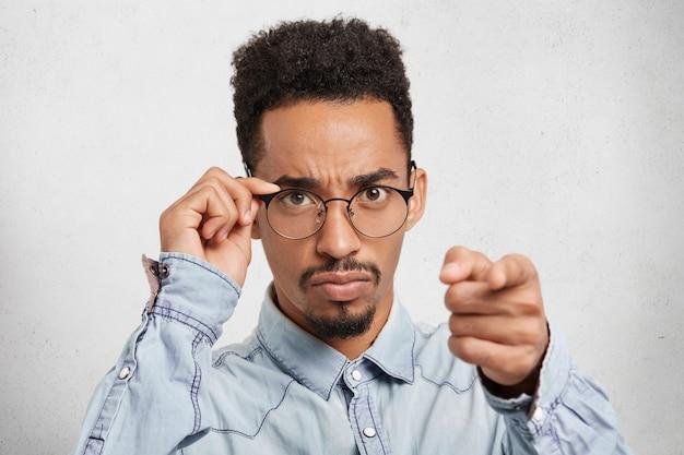 Wybieram ciebie! poważny, surowy przedsiębiorca płci męskiej wydaje polecenia kolegom