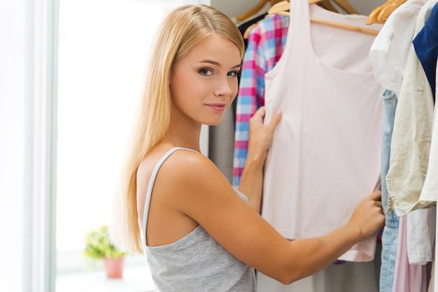 Wybieram strój na dziś. uśmiechnięta młoda kobieta wybierająca ubrania i patrząca na kamerę