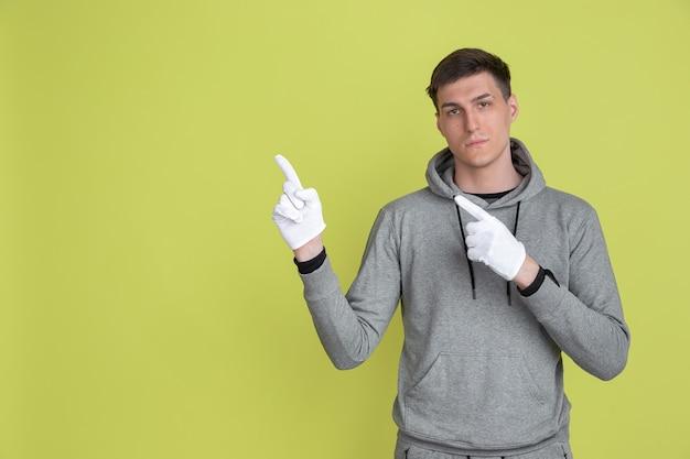 Wybieram, wskazuje na bok. portret mężczyzny rasy kaukaskiej na białym tle na ścianie studio żółty. mężczyzna za pomocą rękawiczek.